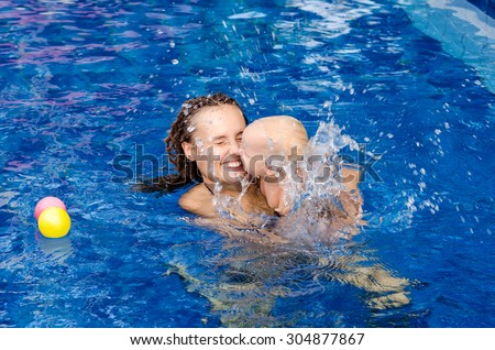 Mother and baby play with ball in the swimming pool - stock photo
