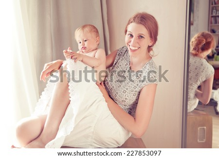 Mother and baby playing in the room. reflection in the mirror - stock photo