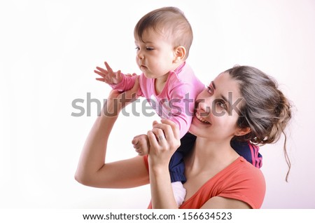 Mother and baby playing. the mother takes the baby in her arms - stock photo
