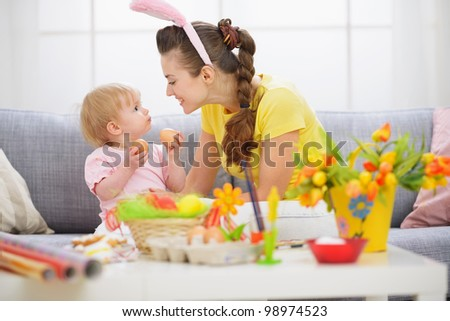 Mother and baby playing with Easter eggs - stock photo