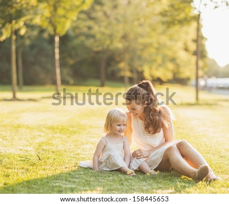 Mother and baby relaxing in park - stock photo