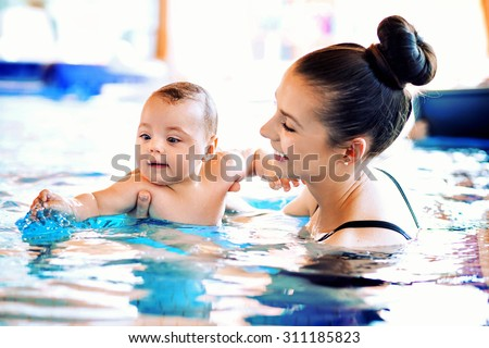 Mother and baby relaxing in the swimming pool - stock photo