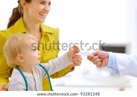 Mother and baby stretching for prescription in hand of pediatric doctor - stock photo