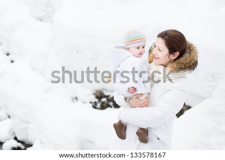Mother and baby walking in a snowy park - stock photo