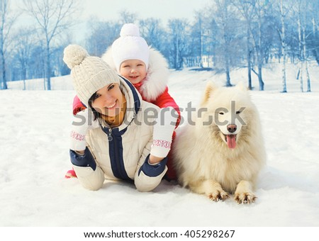 Mother and baby with white Samoyed dog together on snow in winter day - stock photo