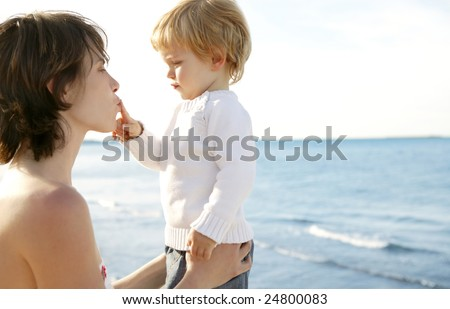Mother and blond son playing happy on the winter ocean beach - stock photo