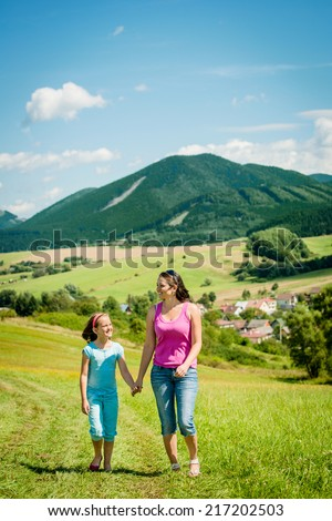 Mother and child are walking and talking in nature on sunny summer day - stock photo