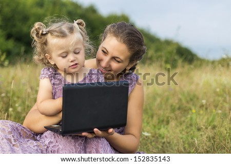 mother and child at a laptop on the nature - stock photo