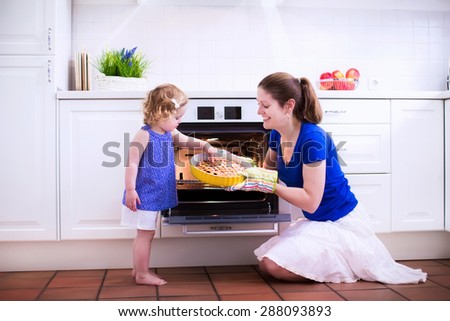 Mother and child bake a pie. Young woman and her daughter cook in a white kitchen. Kids baking pastry. Children helping to make dinner. Modern interior with oven and other appliances. Family eating. - stock photo