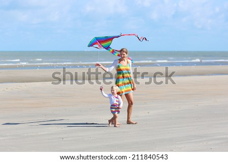 Mother and child concept: young beautiful woman and her lovely cute toddler daughter playing together on the beach flying colorful kite, North Sea, Belgian coast - stock photo