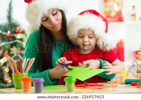 Mother and child cut christmas tree from paper preparing to holiday - stock photo
