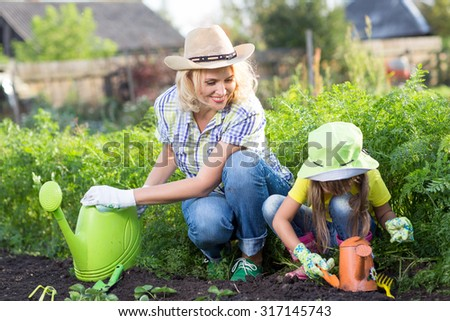 Mother And Child Daughter Planting Seedling In Ground On Allotment - stock photo