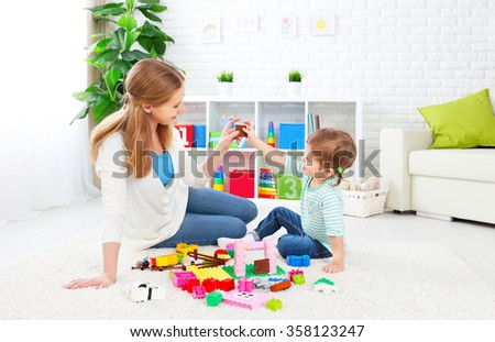 Mother and child daughter playing together, build from the constructor - stock photo