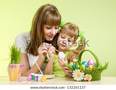 mother and child girl paint easter eggs over green background - stock photo