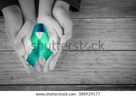Mother and child hand hold blue ribbon awareness liver Bile Duct Cancer Awareness loop symbolic logo raising support help people life living - stock photo