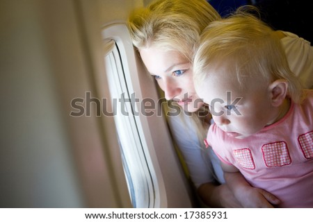 mother and child look through the window of the airplane - stock photo