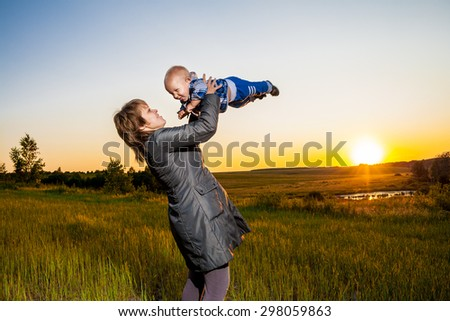 mother and child looking at the sunset - stock photo