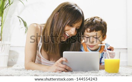 Mother and child on a carpet stretched with pad and orange juice./ Mother and son having fun with a digital tablet in home - stock photo