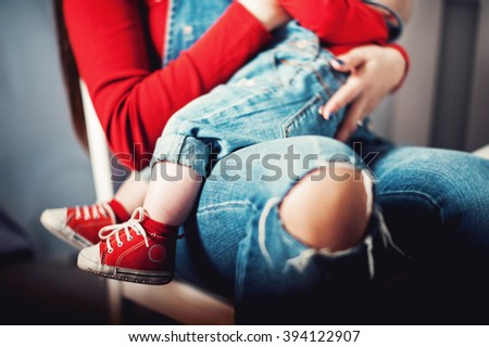 mother and child on a chair dressed in blue jeans and red sneakers in a sitting position - stock photo