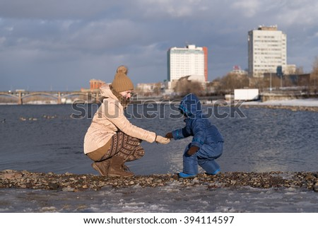 Mother and child on a river bank - stock photo