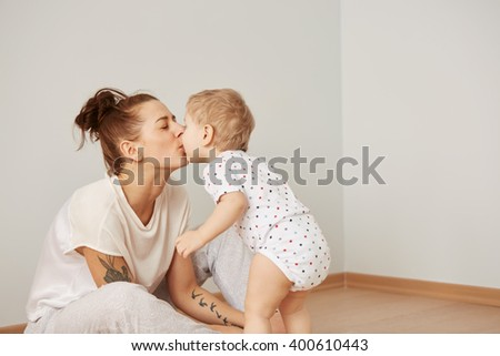 Mother and child on a white bed. Mom and baby boy in diaper playing in sunny bedroom. Parent and little kid relaxing at home. Family having fun together at the weekend together. Selective focus - stock photo