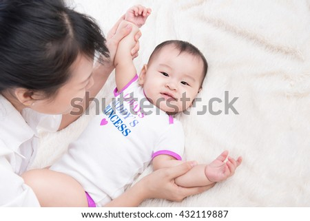 Mother and child on a white bed. Mom and baby girl playing. Parent and little kid relaxing at home. Family having fun together. Bedding and textile for infant nursery. - stock photo