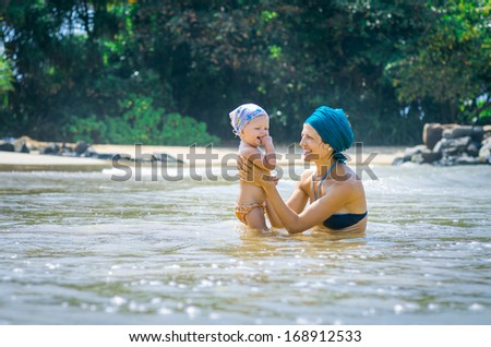 Mother and child on the beach - stock photo
