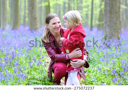 Mother and child outdoors. Happy family of two, young smiling woman and her cute toddler daughter enjoying beautiful day in the forest with bluebells flowers - stock photo