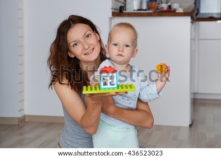 Mother and child  playing and discovery at a home interior - stock photo