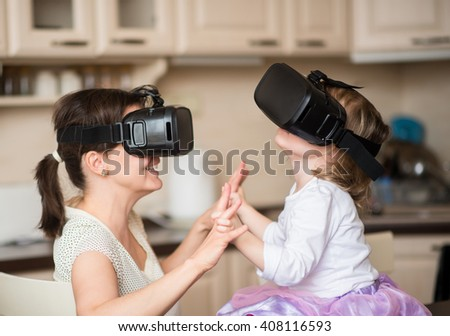 Mother and child playing together with virtual reality headsets indoors at home - stock photo
