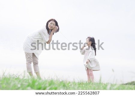 Mother and child playing with a string telephone - stock photo