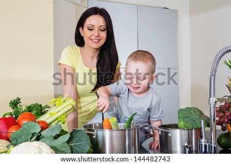 Mother and child preparing soup - stock photo