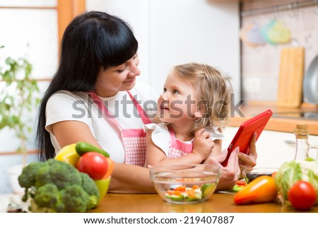 Mother and child preparing vegetables together at kitchen and looking at tablet for receipe - stock photo