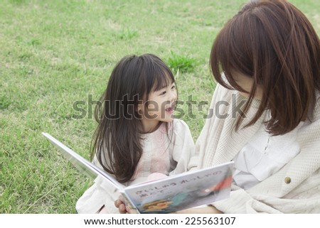 Mother and child reading the picture book on the grass - stock photo