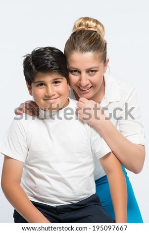 Mother and child son sitting and posing while hugging each other - stock photo