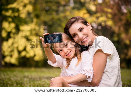 Mother and child taking selfie photo with phone camera outdoor in nature - stock photo