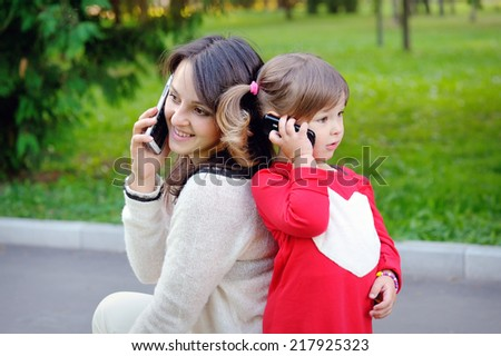 Mother and child talking on the phone - stock photo