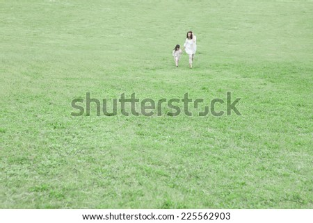 Mother and child walking on the grass - stock photo