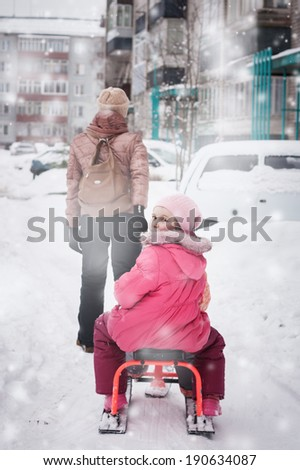 Mother and child walking through the city under snowfall. - stock photo