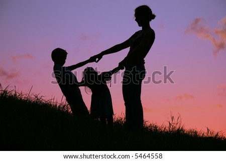 mother and children are held for the hands on the sunset - stock photo