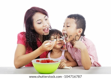 Mother and children eating healthy snack - fruit salad . Shot in studio isolated on white - stock photo