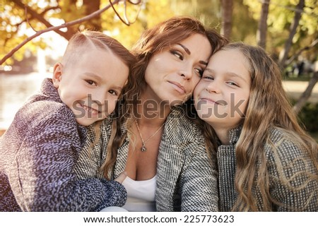 Mother and children in autumn park under a tree. - stock photo