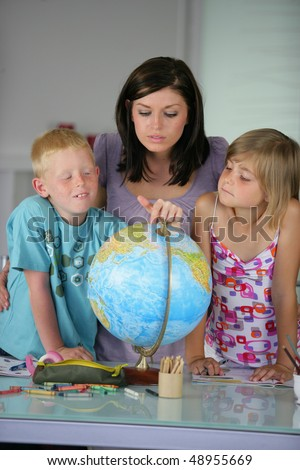 Mother and children looking at educational globe - stock photo