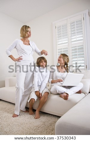 Mother and children on sofa using laptop - stock photo