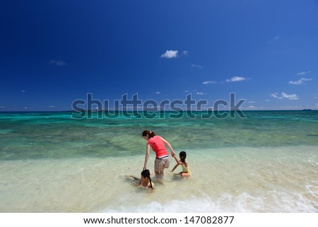 Mother and children playing at the beach - stock photo
