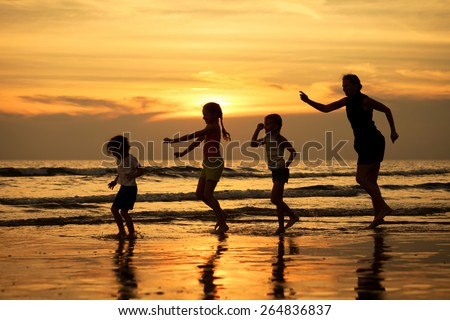 Mother and  children playing on the beach at sunset time. Concept of friendly family. - stock photo