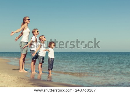 Mother and  children playing on the beach. Concept of friendly family. - stock photo