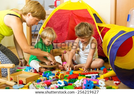 Mother and children playing with  toys indoor - stock photo
