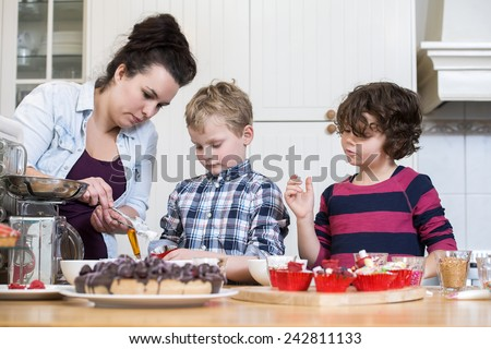Mother and children preparing cupcake in kitchen - stock photo