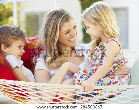 Mother And Children Relaxing In Garden Hammock Together - stock photo